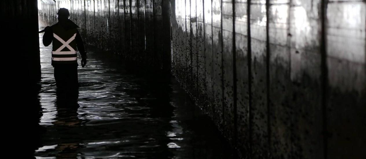Técnico em uma galeria subterrânea da Zona Portuária: especialistas apontam soluções diferentes para os alagamentos que castigam o Rio durante temporais. Em algumas regiões da cidade, não há redes de drenagema Foto: Custódio Coimbra / Agência O Globo