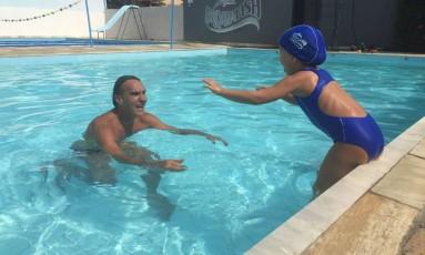 Beto Rodrigues com a neta Cora, a quem ensinou a nadar: pioneiro da natação de bebês na cidade Foto: Divulgação/Betina Kopp