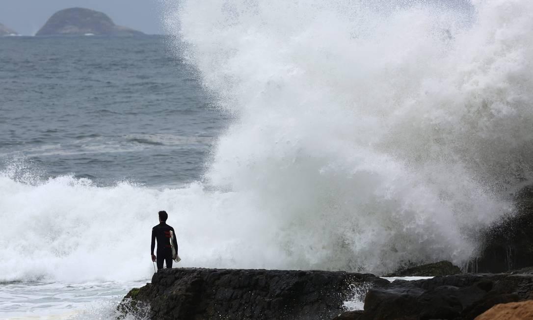 Surfista observa as ondas que batem na pedra na Praia do Leblon: se atreverá a entrar no mar? Foto: Custódio Coimbra / Agência O Globo