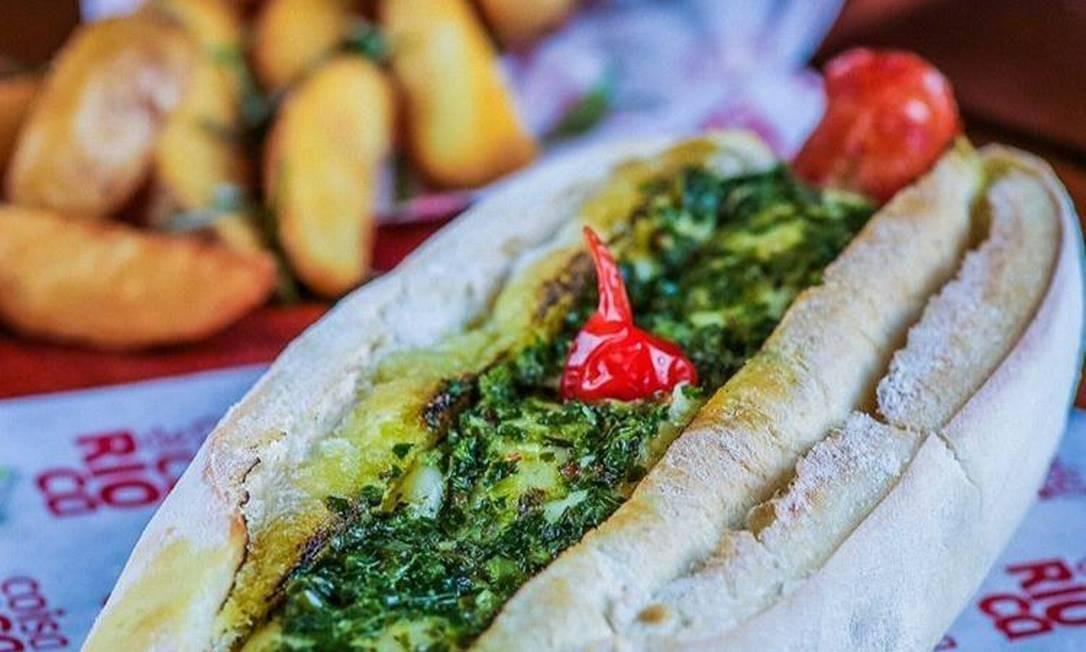 O cachorro-quente Jonns Dog (R$ 24), da Coisa de Carioca, é feito de linguiça artesanal de pernil com queijo gratinado e molho chimichurri, servido no pão de baguete umedecido com salsa de mostarda e grãos dijon Foto: Divulgação/Emi Parente