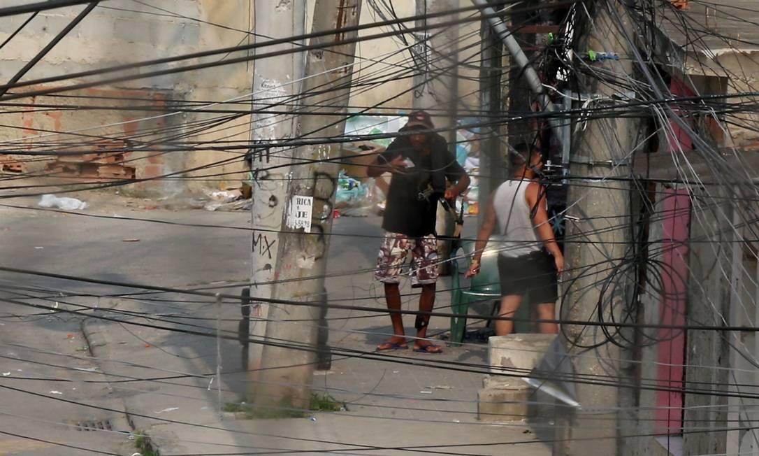 Homem com tornozeleira eletrônica e fuzil na Cidade de Deus. Homem ao seu lado também está com armado com uma pistola Foto: Fabiano Rocha / Agência O Globo