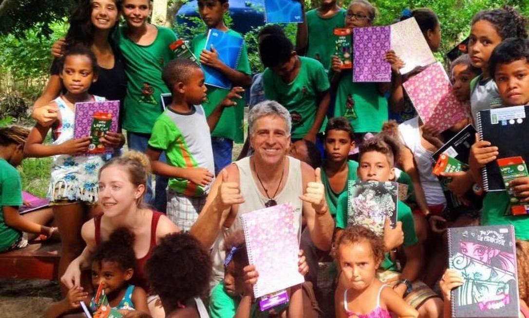 Carl André com crianças durante uma ação. O construtor de pranchas reúne cerca de 40 cestas básicas por mês para o projeto Foto: Acervo pessoal/Carl André