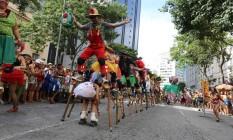 Um grupo de equilibra sobre pernas de pau, enquanto a folia passa sob eles de patins: irreverência no Vem cá minha flor Foto: Marcia Foletto / Marcia Foletto