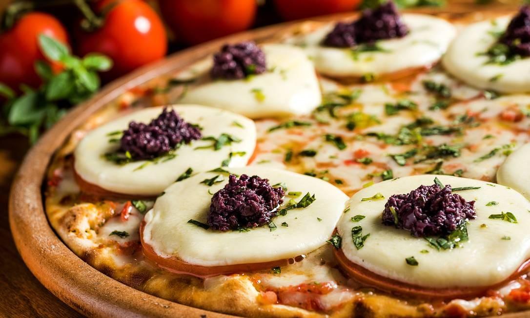 Camelo. Aberta há um ano no Rio, a casa reduziu em 15% o valor das pizzas. O desconto vale, desde agosto, para sabores como Copacabana (mozzarella de búfala, peito de peru, alho-poró, tomate e azeitonas pretas), que caiu de R$ 89 para R$ 75,65 (a grande). Av. Henrique Dumont 57, Ipanema (2274-2303). Seg a qui, das 18h às 23h30m. Sex e sáb, das 18h à 1h. Dom, do meio-dia à meia-noite. Foto: Filico / Divulgação