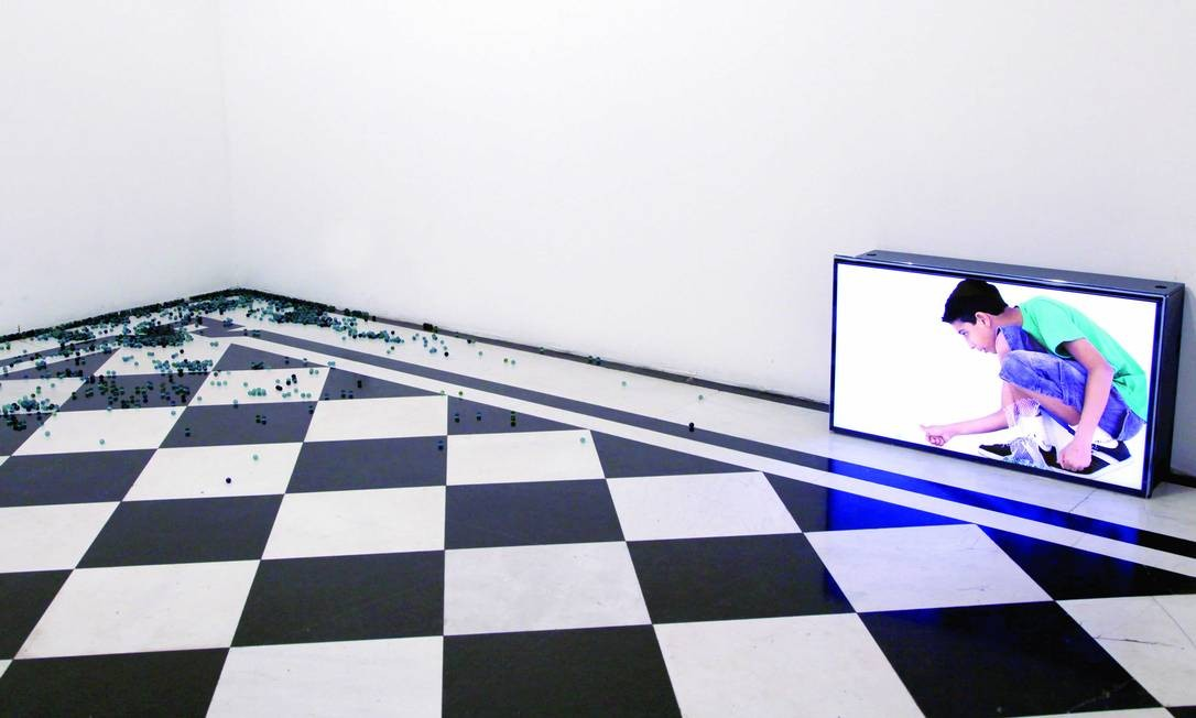 """A artista plástica brasileira Celina Portella explora as fronteiras entre o virtual e o real em """"Vídeo-Boleba"""": meninos, em tamanho natural, """"lançam"""" bolinhas de gude de dentro da TV para o chão. Divulgação"""