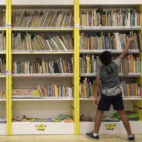 Criança pega um livro na Biblioteca Infantil Maria Mazzetti Foto: Gustavo Miranda / Agência O Globo