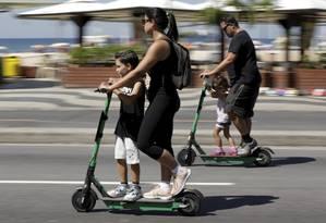 Pais dividem patinetes elétricos com os filhos: prática é proibida Foto: Custódio Coimbra / Agência O Globo