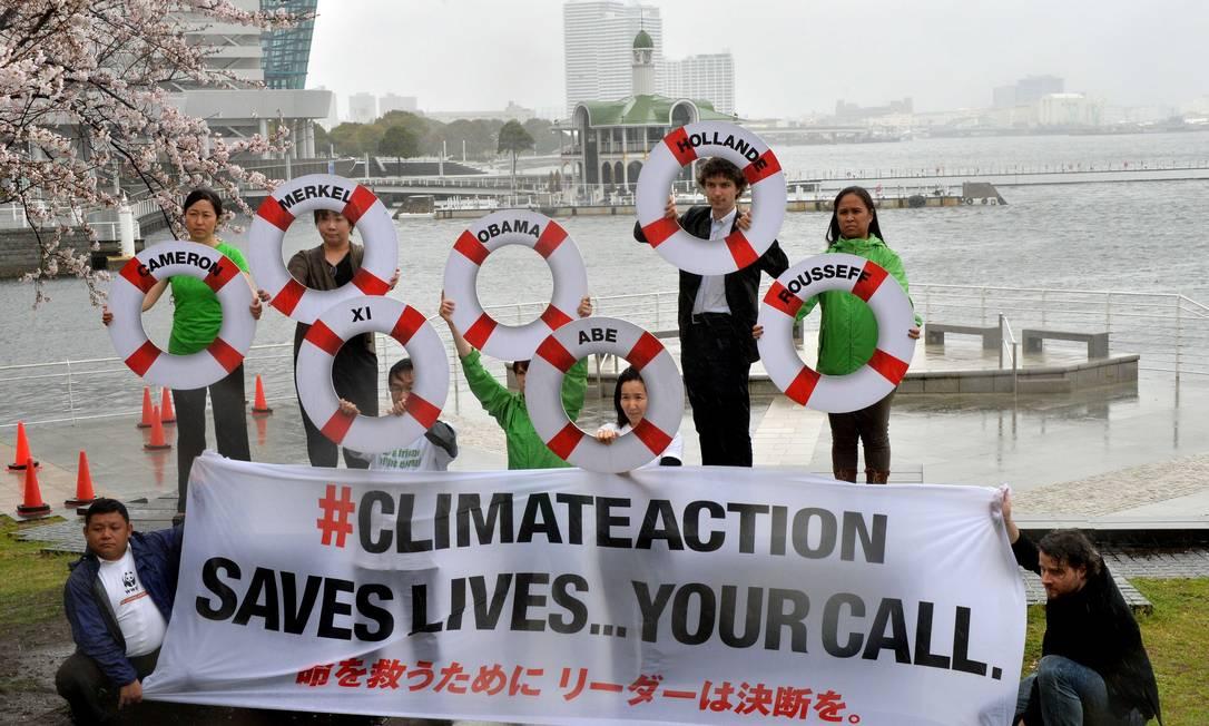 Integrantes do Greenpeace mostram cartaz com a mensagem 'Ação climática salva vidas... Você decide' e boisas salva-vidas com os nomes de líderes mundiais. O protesto contra o aquecimento global aconteceu perto do Painel Intergovernamental de Mudanças Climáticas (IPCC) Foto: YOSHIKAZU TSUNO / AFP