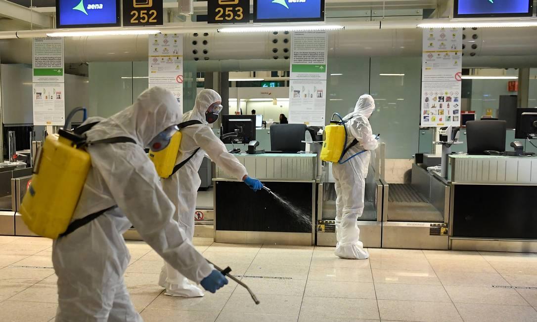 Membros da unidade militar de emergências da Espanha atuam na desinfecção de aeroporto de Barcelona: crise do coronavírus se alastrou pelo mundo e tem cobertura diária do GLOBO Foto: Josep Lago / AFP